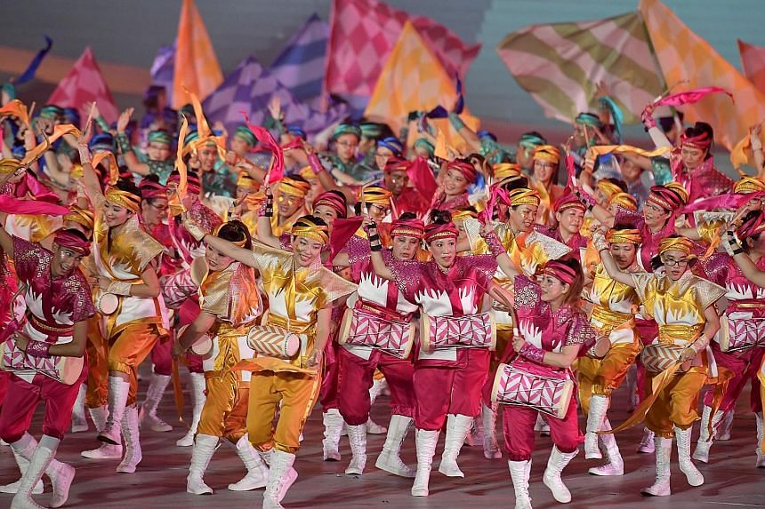 """The audience (right) taking part in the Placard Challenge, where they used the red and white placards in their funpacks to form the words """"We Are Singapore"""" across the floating platform. Performers from the People's Association (far right) raising ex"""