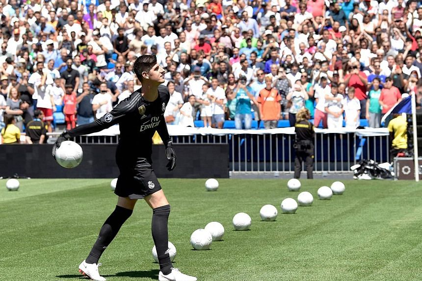 Belgian goalkeeper Thibaut Courtois throwing balls to spectators during his presentation as a Real Madrid player at the Santiago Bernabeu stadium in Madrid yesterday. He had refused to turn up for training at Chelsea earlier this week in a bid to for