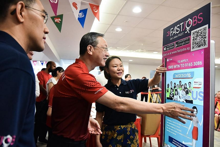 Ms Joelle Pang, start-up FastJobs' regional business development director, showing Radin Mas MP Sam Tan how to use a FastKiosk at the Radin Mas Community Club yesterday. The kiosk lists job vacancies in the Radin Mas neighbourhood.