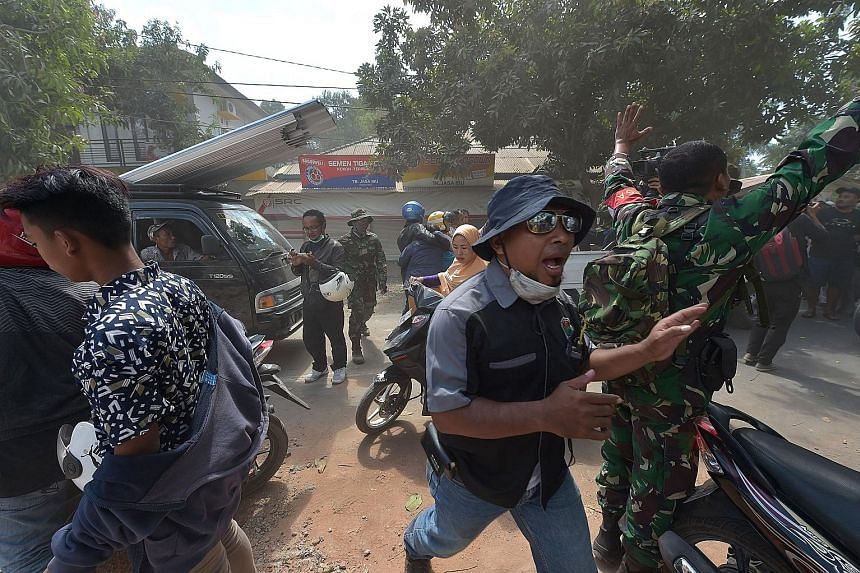 An Indonesian official and a soldier trying to calm people after an aftershock hit an area in Tanjung, Lombok island, yesterday. The latest magnitude-6.2 earthquake was among hundreds of aftershocks following a magnitude-7 earthquake on Sunday.