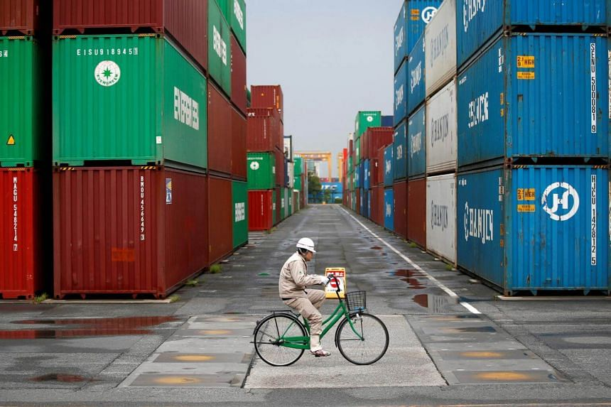 A file photo of a worker riding a bicycle in a container area at a port in Tokyo.