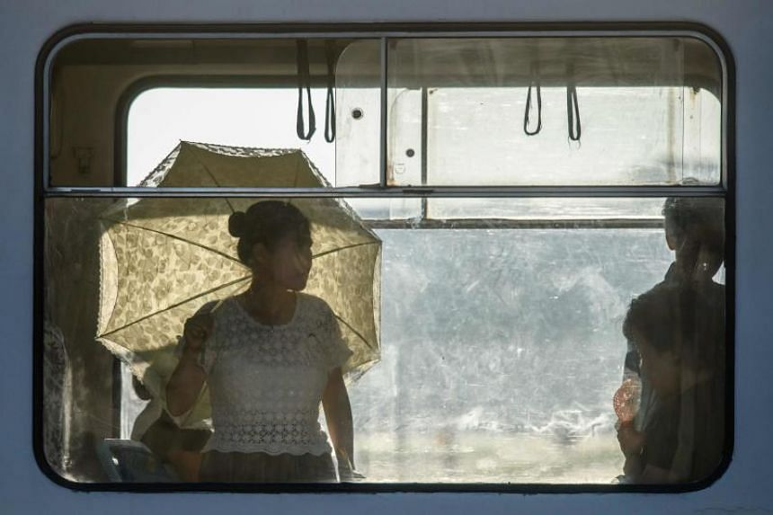 A commuter shields herself from the sun with a parasol as she rides a tram in Pyongyang on July 24, 2018. There has been no rainfall since early July as temperatures soared to an average 39 deg C across the country,
