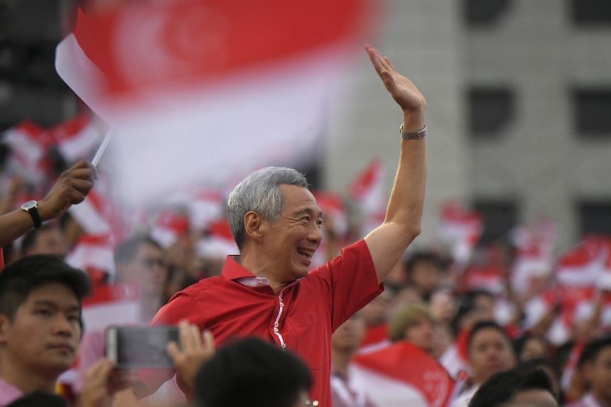 Prime Minister Lee Hsien Loong waving to the crowd as he and other MPs make their way to their seats to watch the parade.