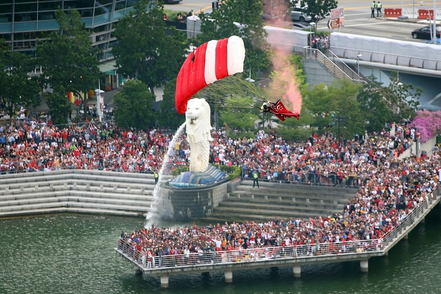 It's a bird, it's a plane, it's a Red Lion ... The army's Red Lions are greeted with thunderous applause as they whizz through the air past the Merlion before landing on the Marina Bay floating platform.