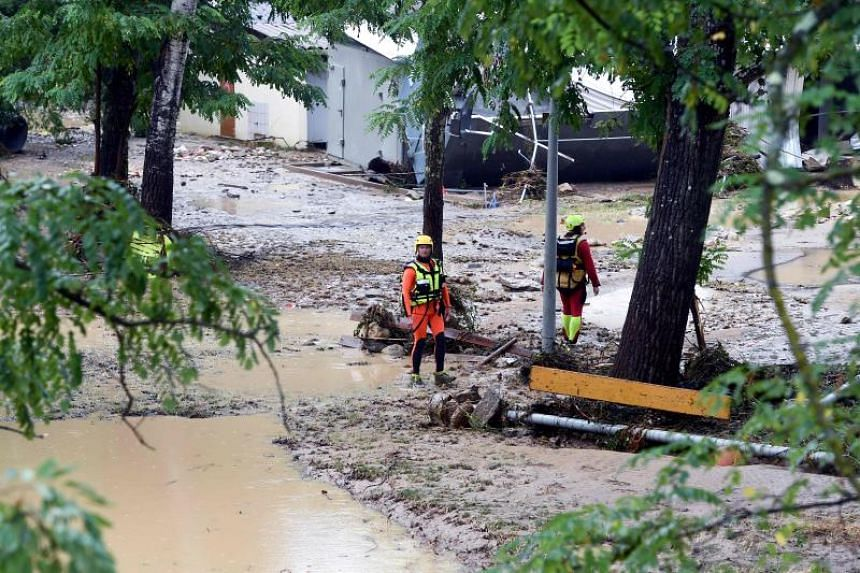Rescuers in a flooded area of a campsite in Saint-Julien-de-Peyrolas as storms and heavy rains sweep across France on Aug 9, 2018.