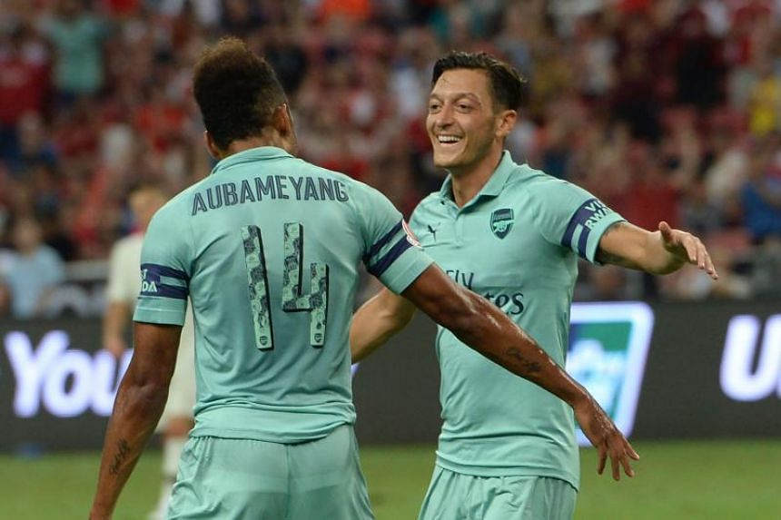 Arsenal's Mesut Ozil (right) celebrates with teammate Pierre-Emerick Aubameyang after scoring during the International Champions Cup football match between Arsenal and Paris Saint-Germain in Singapore on July 28, 2018.