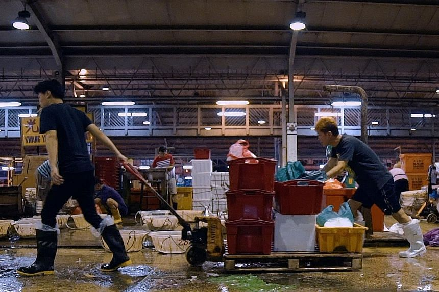 Fishmonger Marcus Phang (left) leaving Jurong Fishery Port with his selection from the day's catch, before packing and distributing the fresh seafood to three wet market stalls. He is one of five Singaporeans featured in Before 10am, a mini video ser