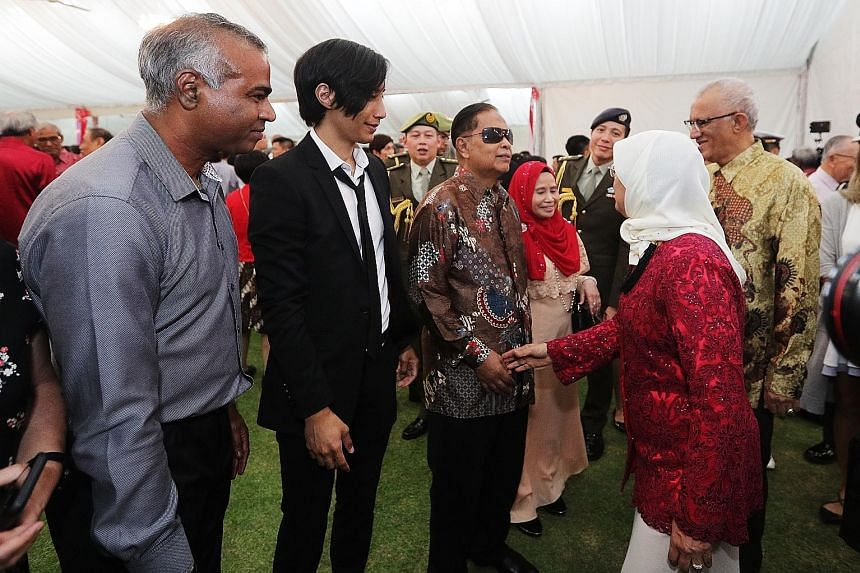 President Halimah Yacob and her husband Mohamed Abdullah Alhabshee met inspiring everyday Singaporeans who were featured in this year's National Day Parade at a National Day reception at the Istana yesterday. They included (from left) Mr Veera Sekara