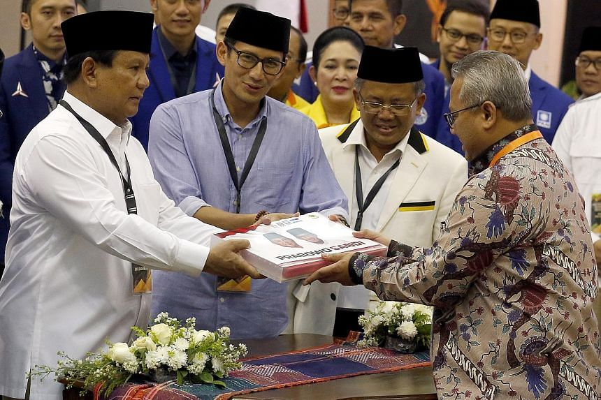 Presidential candidate Prabowo Subianto (left) and running mate Sandiaga Uno (beside him) filing their papers in Jakarta yesterday. With them is Prosperous Justice Party chairman Sohibul Iman (second from right).