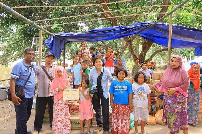 Singapore Red Cross volunteers Kamaraj Pandian (far left) and Lee Siew Yian (centre) with residents on Thursday in a village in West Lombok, where they are helping with relief efforts.