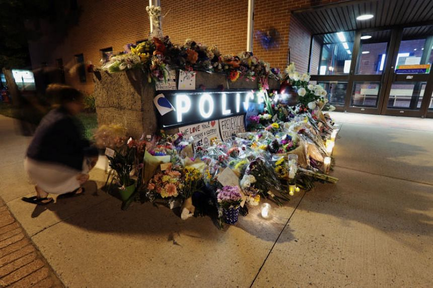 Fredericton residents pay their respects at a makeshift shrine created in front of police headquarters after four people were killed in a shooting in Fredericton, New Brunswick, Canada, on Aug 10, 2018.