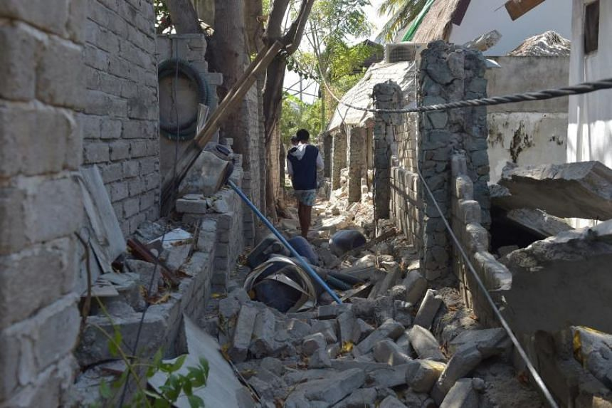 A man walks through the rubble of damaged buildings on Gili Air island, after the region was hit by several quakes, on Aug 11, 2018.