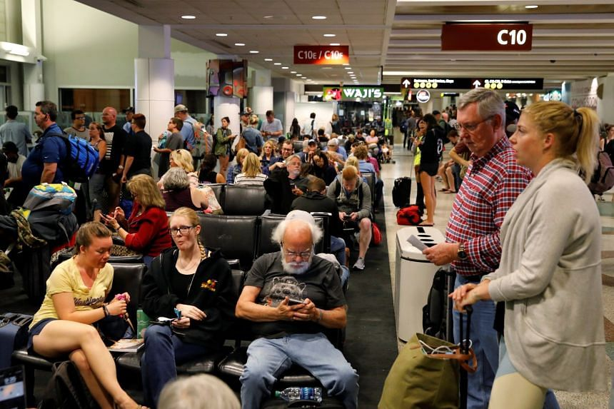 Passengers waiting in the terminal of Seattle-Tacoma International Airport after an incident where an airline employee made an unauthorised takeoff in an airplane, on Aug 10, 2018.