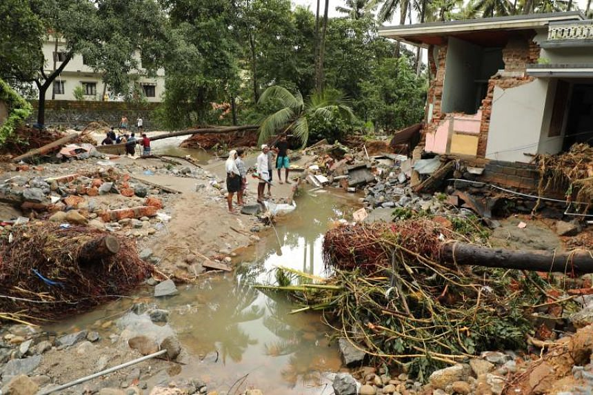 Indian residents look at houses destroyed by flood waters at Kannappankundu in Kozhikode, in the Indian state of Kerala, on Aug 10, 2018.
