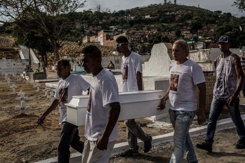The funeral of Vitor Gabriel, 3, at a cemetery in São João de Meriti in Rio de Janeiro, Brazil, in 2017. A stray bullet killed him while he was watching television at home.
