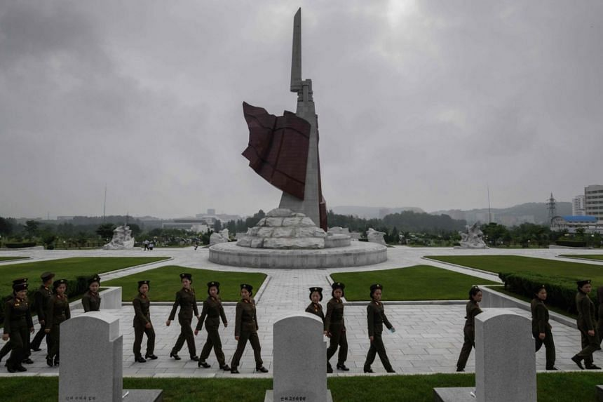 Korean People's Army soldiers walk before graves at the Fatherland Liberation War Martyrs Cemetery on the anniversary of the end of the Korean War, in Pyongyang, on July 27, 2018.