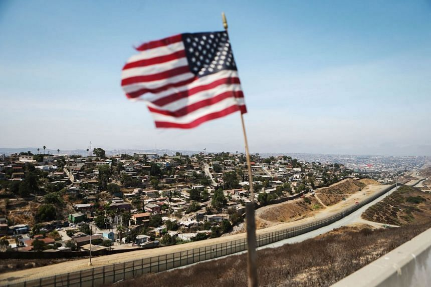 An American flag flies along a section of the US-Mexico border, with the Mexican city of Tijuana in the background, on July 16, 2018, in San Diego, California.