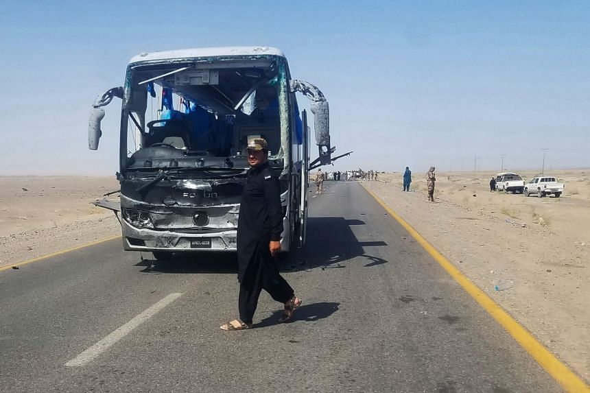 Security personnel walk next to the damaged bus after a suicide attack in Dalbandin region.