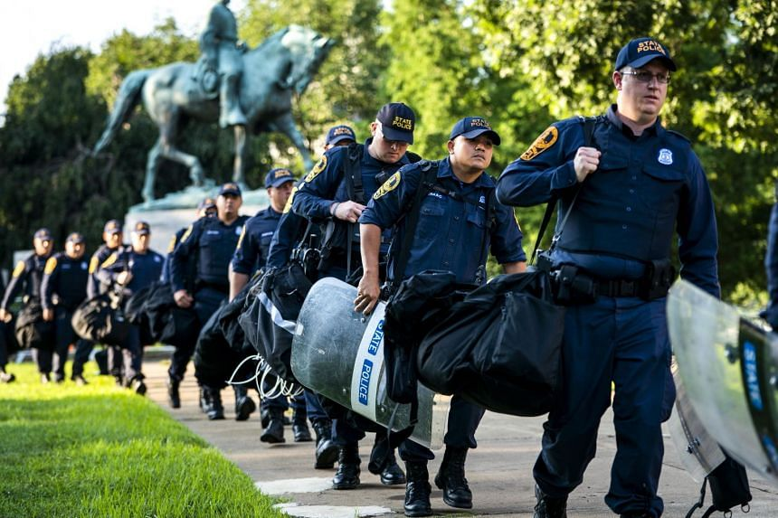 Police officers prepare to set up a perimeter to prevent a repeat of last year's Unite the Right rally in downtown Charlottesville, in which three people died and dozens were injured.