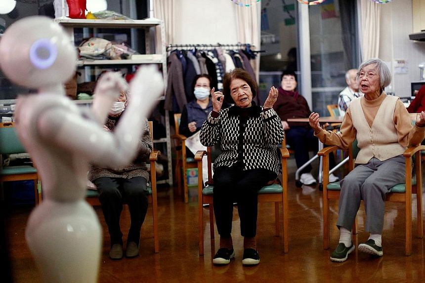 Senior citizens following moves made by humanoid robot Pepper during an exercise routine at Shin-tomi nursing home in Tokyo. The phrase hyakunen jinsei (100-year life) has bustled into Japan's corporate vocabulary; in some cases, such as manufacturin