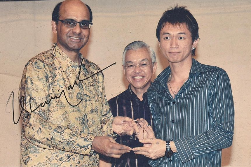 Mr Kim receiving a Taman Jurong commendation award for community service in 2009 from Deputy Prime Minister Tharman Shanmugaratnam, who also signed this picture for him.
