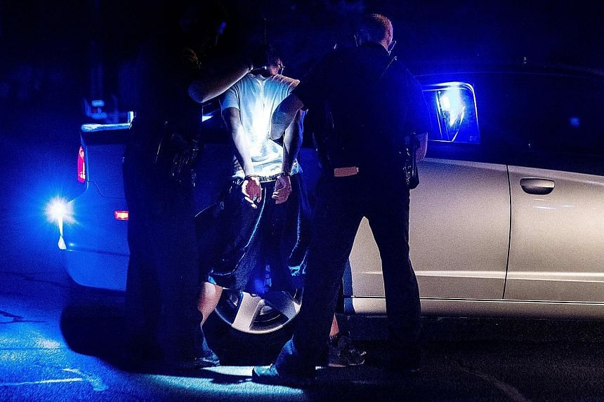 Northern Virginia Gang Task Force and immigration officers arresting an alleged MS-13 gang member in Manassas, Virginia, on Aug 10 last year as part of a national crackdown on gangs.