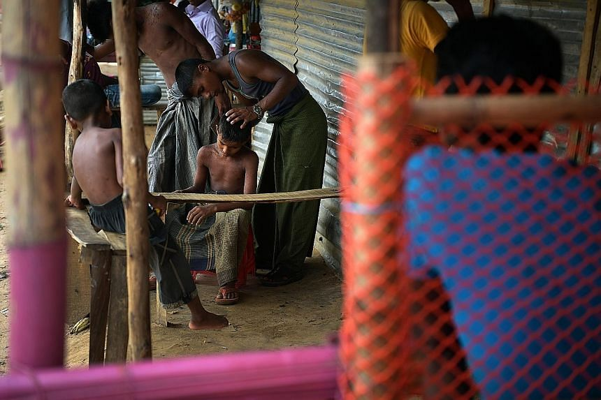 A Rohingya teen taking on the role of a barber, cutting the hair of a young boy at the Kutupalong camp. Rohingya men filling bags with bricks at the Kutupalong camp on July 18. Till earlier this year, some camp residents earned some money by helping