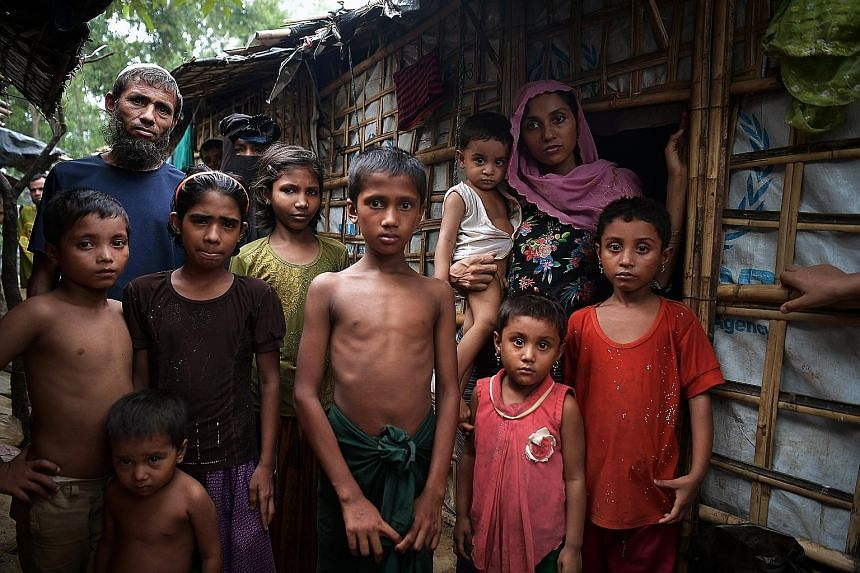 Madam Noor Beghum (right) with her four children and the man who took pity on them and took her family in to live together with his family, outside his home at the Kutupalong camp. Madam Beghum, who saw her husband hacked down, recounts how several s