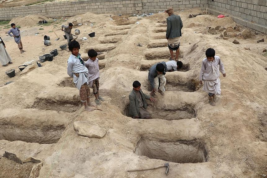 "Boys inspecting graves prepared for the victims - including 40 children - of Thursday's air strike on a bus in Yemen's Saada province. The Arab states, who have announced a probe, initially said the air strike was a ""legitimate military action""."