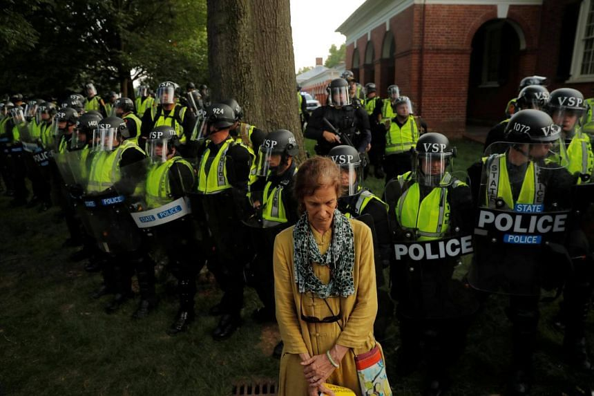 A protester stands in front of Virginia State Police officers forming a cordon at the University of Virginia in Charlottesville, on Aug 11, 2018.