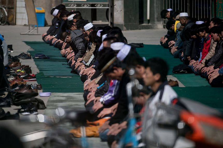 Ethnic Hui Muslim men praying at a mosque during Friday prayers in Linxia, in China's Gansu province.