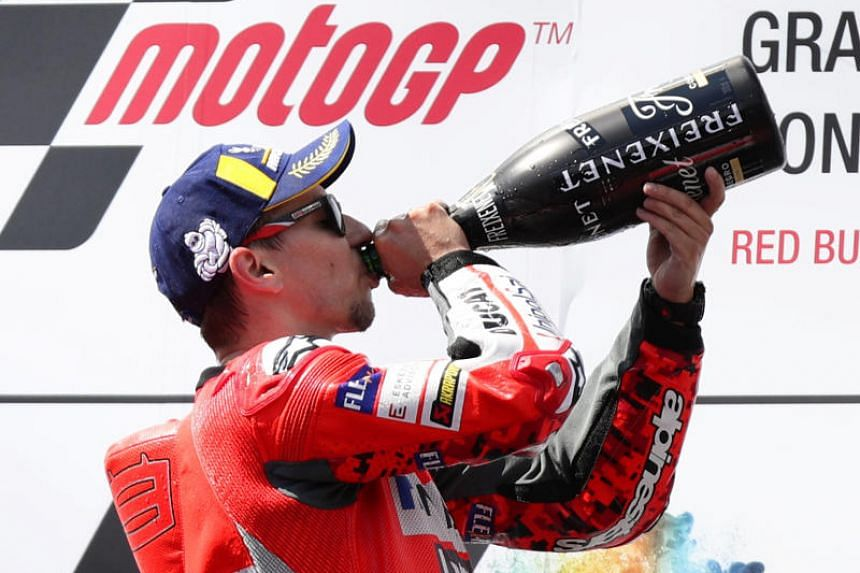 Ducati's Jorge Lorenzo drinks champagne as he celebrates on the podium after winning the Austrian Grand Prix on Aug 12, 2018.