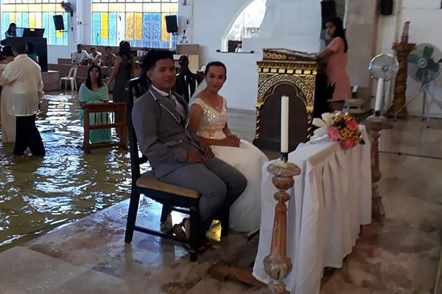 Jobel Delos Angeles and her groom at their wedding in a flooded church in Hagonoy, Philippines, on Aug 11, 2018.