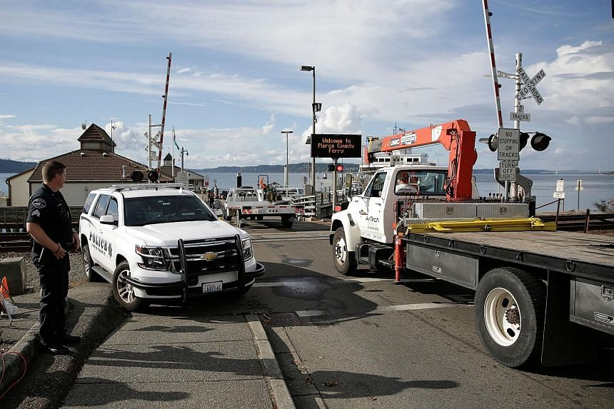 Aircraft retrieval vehicles (left) arriving last Saturday at the Steilacoom ferry dock for the trip to Ketron Island, the crash site of the Horizon Air plane that was stolen from Sea-Tac International Airport in Seattle, Washington. The empty airplan