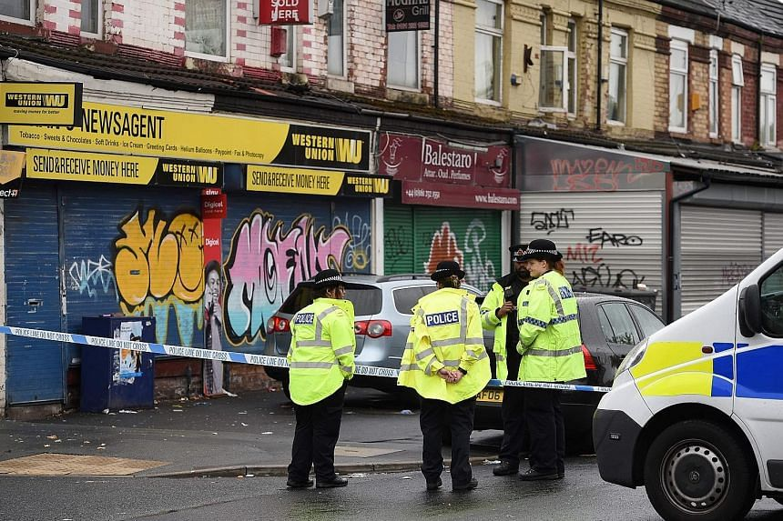 Police officers at the scene of the shooting in the Moss Side neighbourhood of Manchester, where 10 people were hurt.