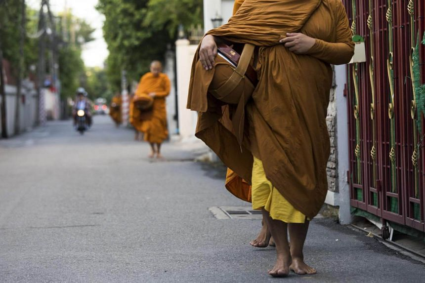 Monks collect food donations during daily almsgiving in Bangkok, on July 4, 2018.