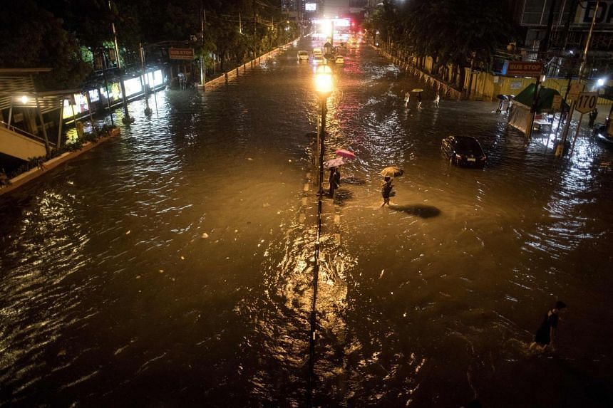 Residents wade through on a flooded street in Manila, on Aug 11, 2018.