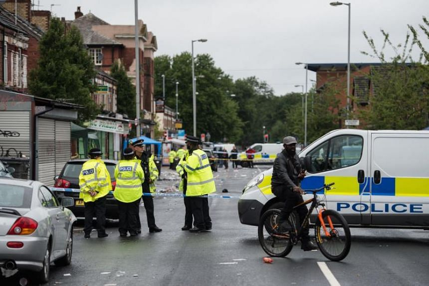 Police officers stand guard at the scene of a shooting at Claremont Road in the Moss Side neighbourhood of Manchester, on Aug 12, 2018.