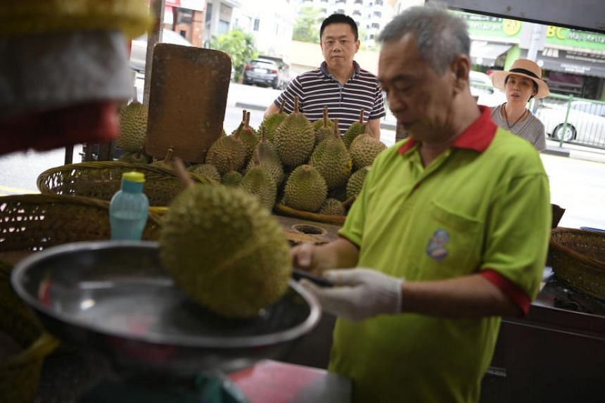 An employee at Combat Durian weighing a durian for a customer on Aug 1, 2018.