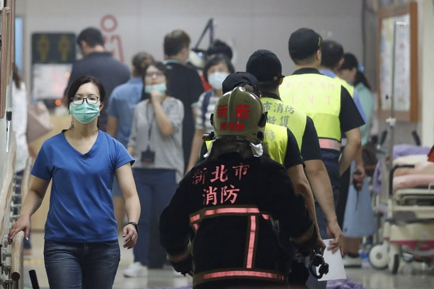 Hospital staff and rescuers evacuating affected patients after a fire broke out in Taipei Hospital, on Aug 13, 2018.