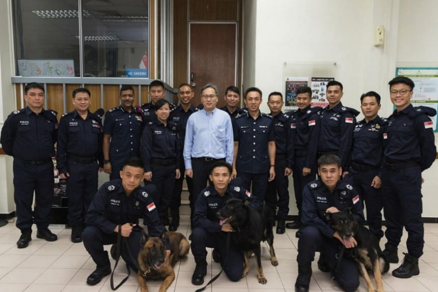 Home Affairs permanent secretary Pang Kin Keong (centre) with the SPF officers and K9 dogs.