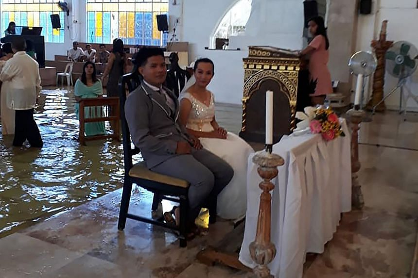 Ms Jobel Delos Angeles and her groom at their wedding last Saturday in a flooded church in Hagonoy town in the Philippine province of Bulacan. She said they did not expect bad weather but never considered calling off the wedding.