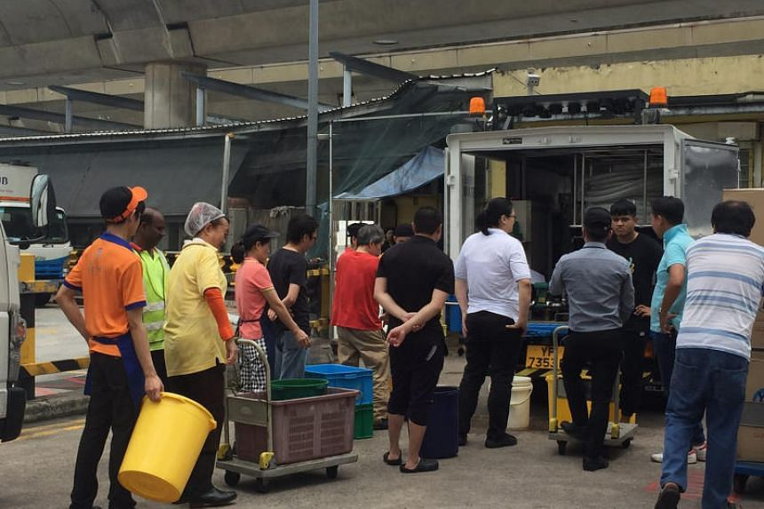 Foodstall operators in and around Tampines Bus Interchange queueing for water from a PUB water wagon after a pipe burst on Nov 3, 2017.