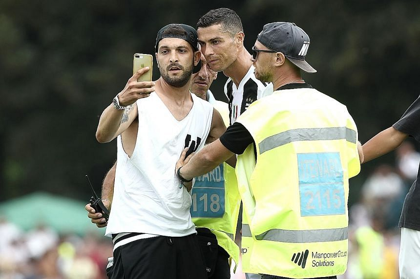 Juventus fans invading the pitch at half-time to take pictures with their new Portuguese star Cristiano Ronaldo.