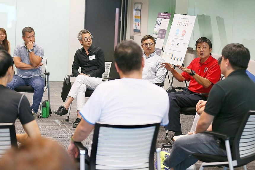 NTUC secretary-general Ng Chee Meng (in red) at a dialogue session with the working committee for the formation of the National Instructors and Coaches Association at the NTUC Centre yesterday. Membership is open to coaches and instructors in industr