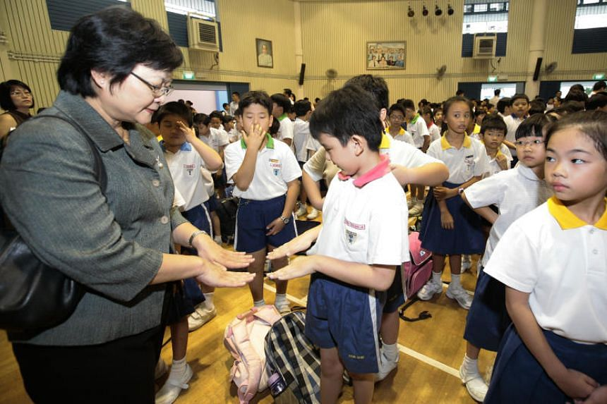 A teacher checking a pupil for HMFD. Symptoms of HFMD include fever, mouth ulcers and rashes on the palms.