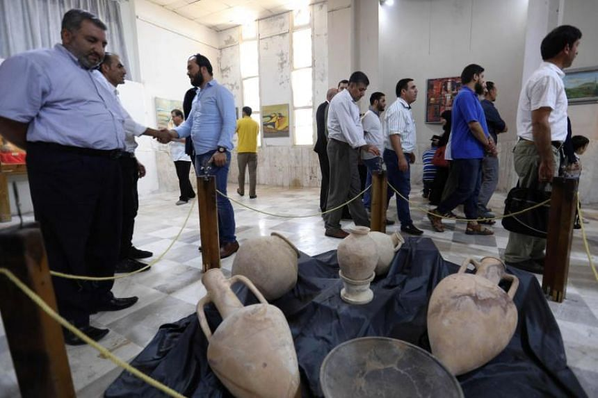 Syrians stroll at the Idlib Museum after it reopened on Aug 13, 2018 in the northern Syrian city of Idlib.