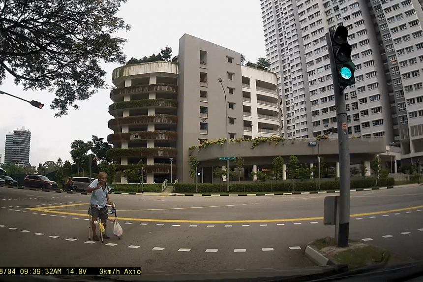 The elderly man holding up his hand several times in appreciation as motorists wait for him to cross.