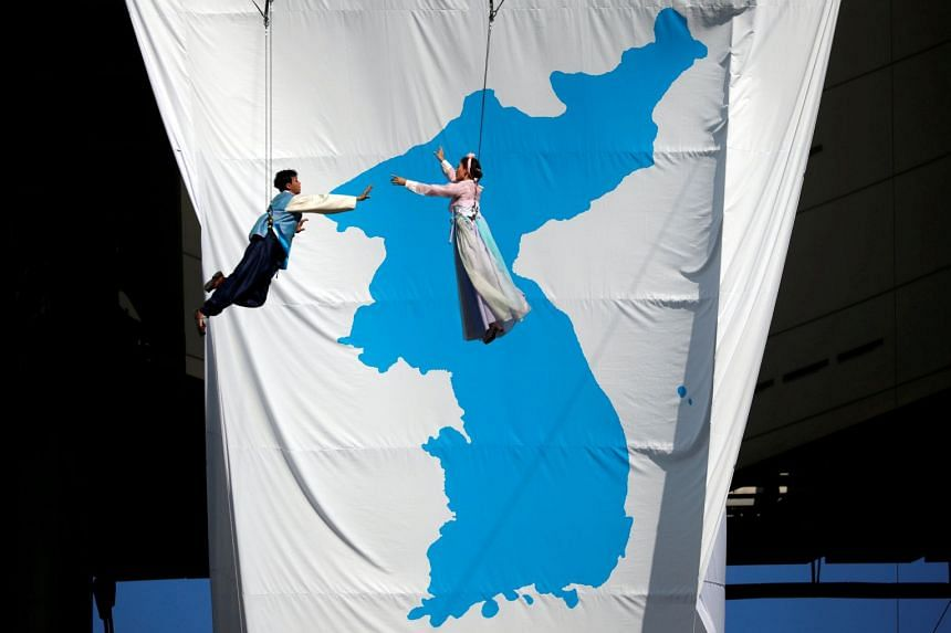South Korean artists perform in front of a giant unification flag before a football match between South and North Korean workers in Seoul, on Aug 11, 2018.