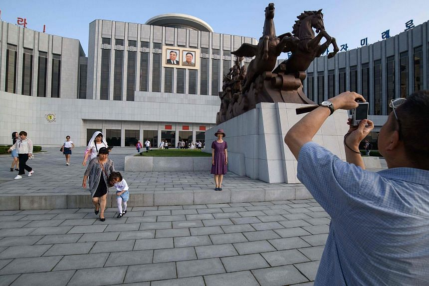 Tourists take photos outside the Children's Palace in Pyongyang, on July 2018.